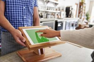 cliente che utilizza il terminale di vendita del touch screen al caffè, fine in su foto