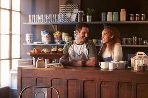 coppia in esecuzione caffetteria in piedi dietro il bancone foto