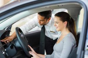 commesso che spiega le caratteristiche dell'automobile al cliente foto