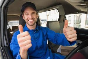 autista consegna sorridendo alla telecamera nel suo furgone foto