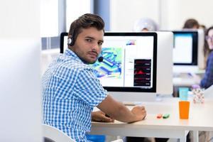 uomo che lavora alla scrivania in ufficio creativo occupato foto
