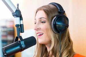 DJ femminile che indossa le cuffie davanti al microfono foto