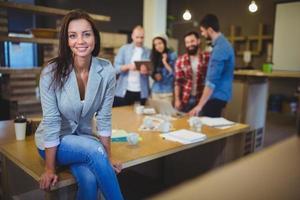 imprenditrice intelligente seduto sul tavolo in ufficio foto