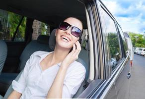 donna felice che per mezzo del telefono foto