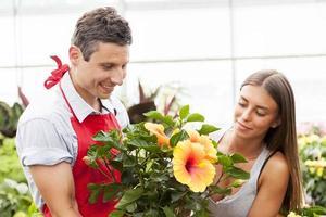 il commesso sorridente vende una pianta ad un cliente grazioso foto