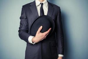 uomo che tiene un cappello a bombetta foto