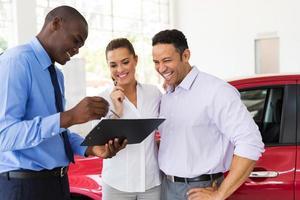 Concessionario d'auto africano che spiega il contratto di vendita alla coppia foto