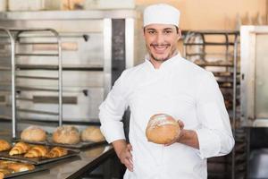 fornaio in possesso di un pane appena sfornato