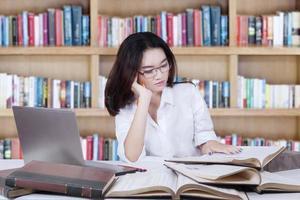 studente seduto in biblioteca durante la lettura di libri foto