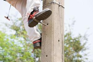 elettricista guardalinee operaio riparatore al lavoro di arrampicata su electri foto