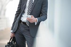 uomo d'affari irriconoscibile tramite smartphone foto