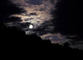 paesaggio notturno con la luna su uno sfondo di montagne foto