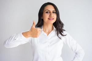 donna graziosa sorridente di affari che mostra pollice in su foto