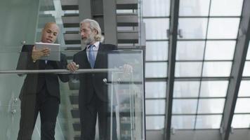 dirigenti aziendali che parlano di affari utilizzando la tavoletta digitale