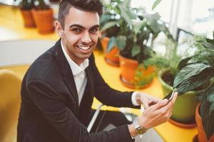 giovane manager positivo che controlla messaggio sul telefono foto