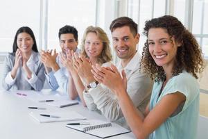 squadra di affari casuali che sorride e che applaude alla macchina fotografica foto