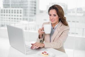 donna di affari allegra che per mezzo del computer portatile alla sua scrivania e tenendo tazza foto