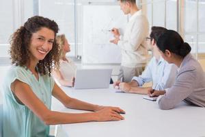donna di affari casuale che sorride alla macchina fotografica nel corso della riunione