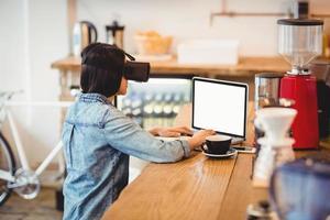 giovane donna che usando l'auricolare di realtà virtuale foto