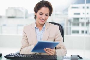 imprenditrice sorridente guardando tablet foto