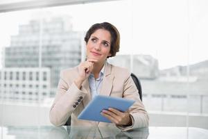 donna di affari premurosa che sorride e che per mezzo della sua compressa digitale foto