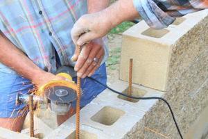 muratore costruisce un muro, smerigliatrice angolare di taglio del tondo per cemento armato foto