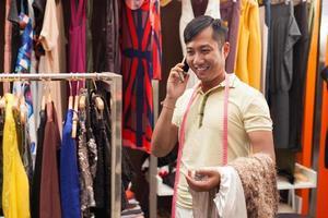 acquisto asiatico della donna che sceglie il negozio di vestito da modo foto