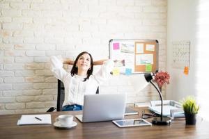 imprenditrice al tavolo appoggiandosi indietro foto