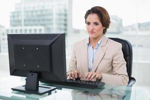 donna di affari severa che si siede davanti al computer foto