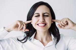 donna d'affari infastidita fermando le orecchie con le dita foto