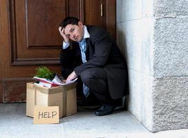 frustrato uomo d'affari sulla strada licenziato portando la scatola di cartone foto