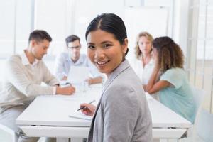 donna di affari casuale che sorride alla macchina fotografica nel corso della riunione foto
