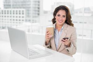 donna di affari allegra che tiene tazza e smartphone eliminabili foto