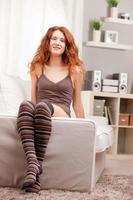 ragazza molto carina intestata rossa seduta sul suo divano foto