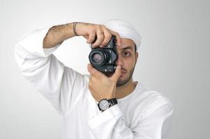 giovane uomo arabo usando tenendo la sua macchina fotografica pronta a sparare,