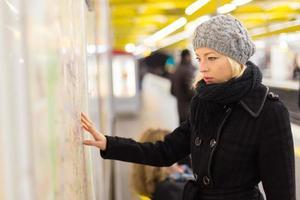 signora cerca sul pannello della mappa dei trasporti pubblici.