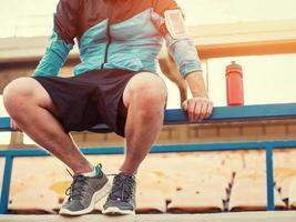 sportivo seduto sulla ringhiera sullo stadio foto