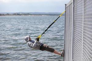 uomo incappucciato all'aperto, allenamento in sospensione al mare foto