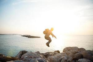il viaggiatore che salta sopra le rocce vicino al mare foto