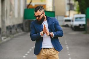 uomo barbuto alla moda cammina attraverso la città foto