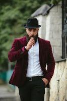 l'uomo ricco con la barba fuma una sigaretta elettronica foto