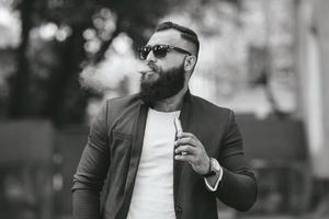 l'uomo con la barba fuma una sigaretta elettronica foto