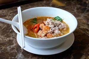 minestra di pasta piccante tailandese in una ciotola (tom yam) foto