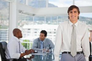 sorridente giovane imprenditore si appoggia sul tavolo foto