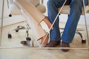 donna di affari casuale che gioca piedino con il collega sotto lo scrittorio foto