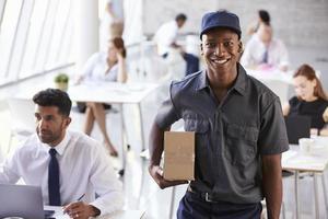 ritratto del corriere che raccoglie pacchetto dall'ufficio occupato foto