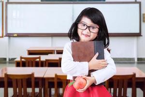il piccolo studente tiene il libro e la mela in classe