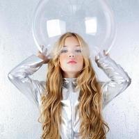 ragazza di astronauta con uniforme d'argento e casco di vetro