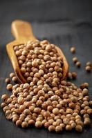 cucchiaio di legno con semi di coriandolo