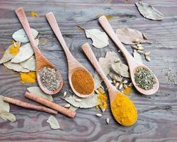 spezie in cucchiai sul tavolo di legno foto